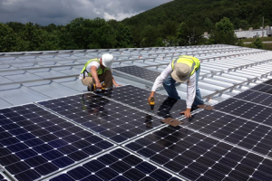 Two Solar Electric Panel Installers on Roof