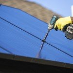 Man Drilling on a Solar Panel