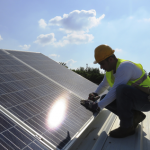 Man Checking Solar PV Installation on Residential Roof